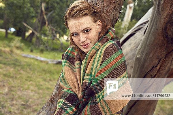 Porträt einer jungen Frau in der Natur in Decke gehüllt