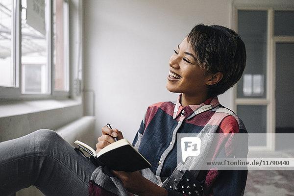 Lächelnde Frau am Fenster sitzend mit Notizbuch