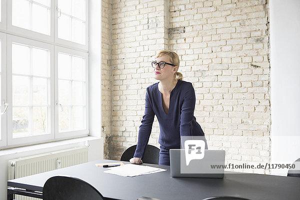 Erfolgreiche Geschäftsfrau steht in ihrem Büro