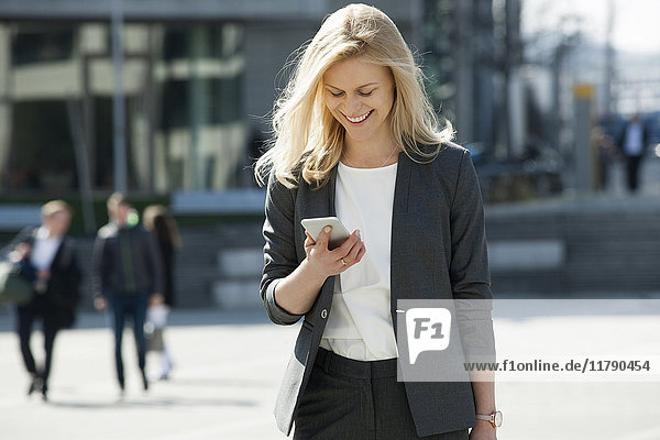 Portrait of smiling blond businesswoman looking at cell phone