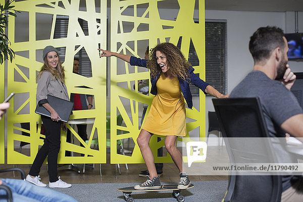 Frau auf dem Skateboard im Büro beim Spaß haben