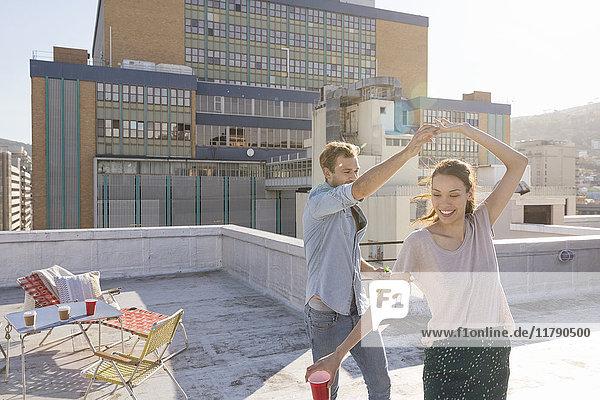 Junges Paar feiert auf einer Dachterrasse  tanzt gemeinsam