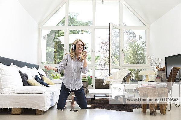 Aufgeregte Frau zu Hause beim Musikhören
