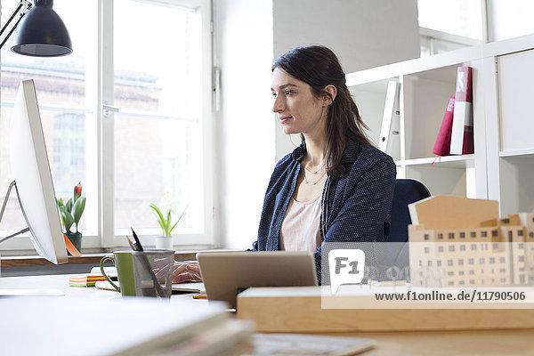 Frau arbeitet am Schreibtisch im Büro
