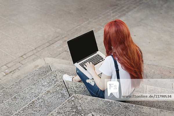 Rothaarige Frau auf der Treppe sitzend mit Laptop