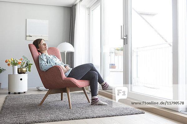 Frau entspannt auf dem Sessel zu Hause
