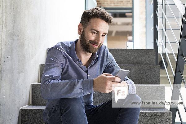 Lächelnder Mann sitzt auf der Treppe und schaut auf das Handy.