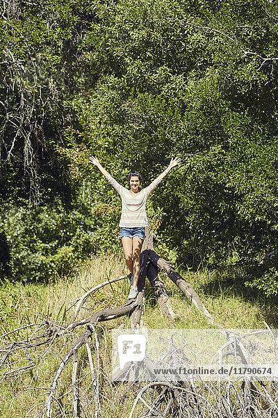 Lächelnde junge Frau balanciert auf Baumstamm