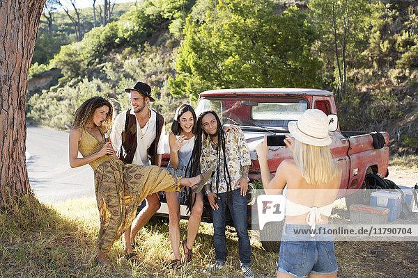Junge Frau macht Handyfoto von Freunden außerhalb des Pick-Up Trucks
