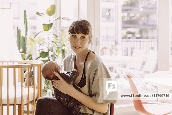 Mother holding her newborn baby boy at home