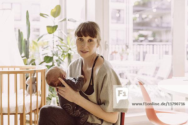 Mutter hält ihr neugeborenes Baby zu Hause.