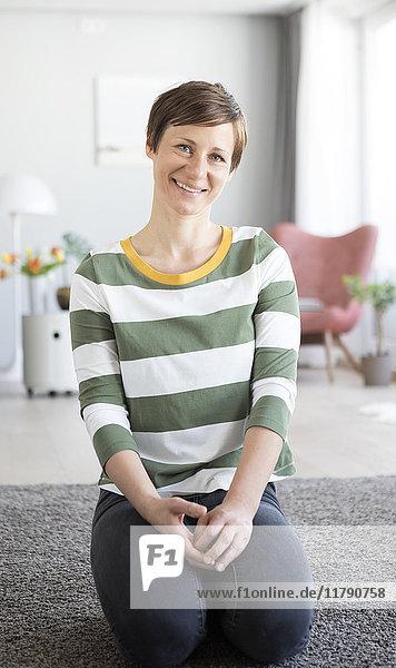 Porträt einer lächelnden Frau  die im Wohnzimmer auf dem Boden sitzt.
