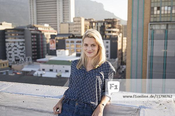 Junge Frau steht auf einer Dachterrasse