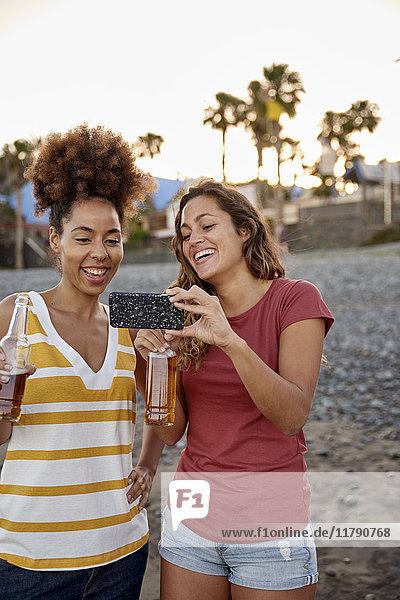 Zwei lachende Freunde mit Bierflaschen  die Selfie am Strand mitnehmen.