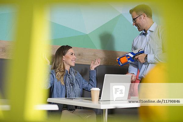 Kollegen haben Spaß im Pausenbereich mit Spielzeugpistole