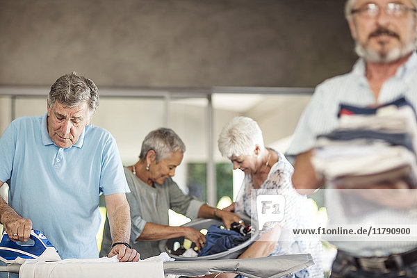 Senioren bügeln Kleidung zusammen