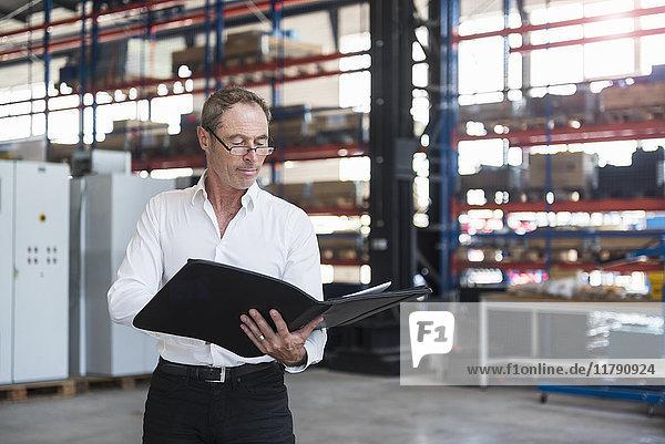 Mann mit Dokumenten in der Fabrikhalle