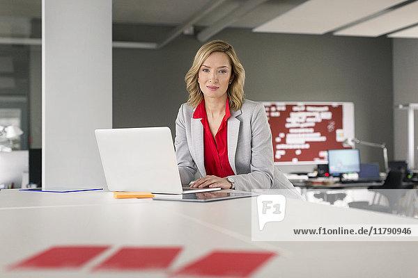 Portrait einer selbstbewussten Geschäftsfrau mit Laptop im Büro