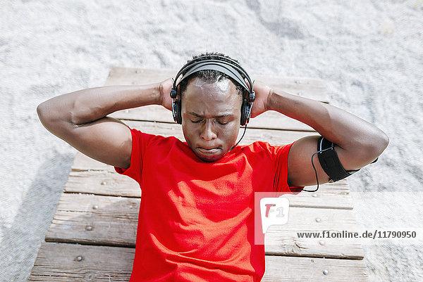Mann  der Sit-ups macht und Musik mit Kopfhörern hört.