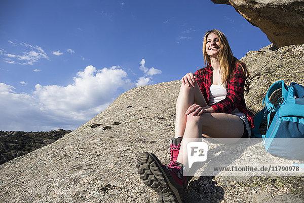 Spanien  Madrid  lächelnde junge Frau auf einem Felsen während eines Trekkingtages