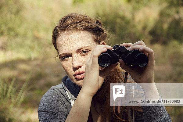 Portrait einer jungen Frau mit Fernglas
