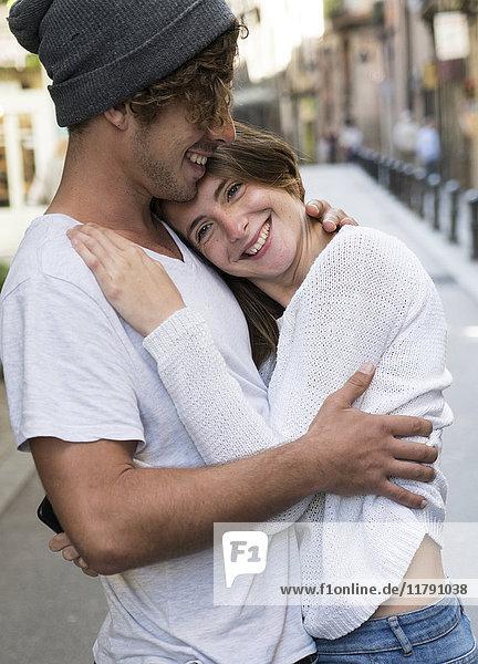 Glückliches junges Paar  das sich in der Stadt umarmt