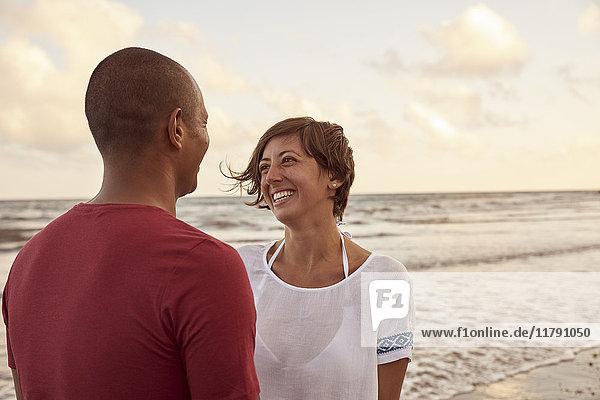 Verliebtes Paar von Angesicht zu Angesicht am Strand in der Abenddämmerung