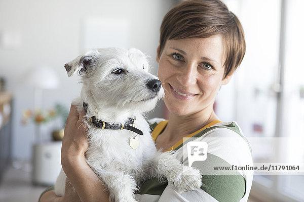 Porträt einer lächelnden Frau  die ihren Hund auf dem Arm hält.