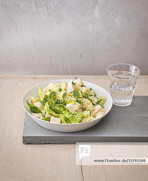 Couscous-Salatteller mit Erbsen  Gurken und gekochtem Hühnerfleisch in Würfel geschnitten