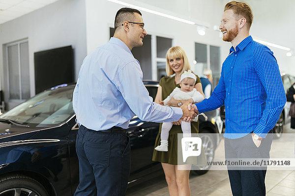Familientreffen Verkäufer von Familienfahrzeugen im Autohaus