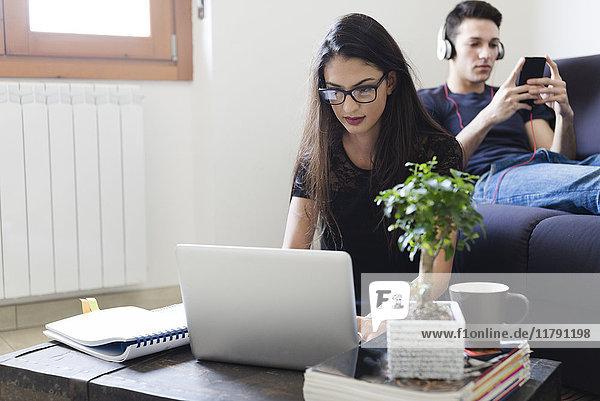 Junge Frau mit Laptop im Wohnzimmer  während ihr Freund auf der Couch mit Handy sitzt.