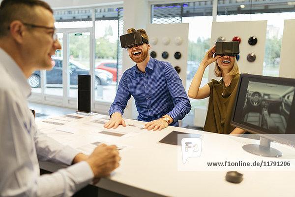 Paar mit VR-Brille im Autohaus