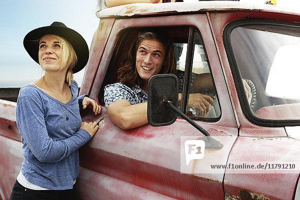 Lächelndes junges Paar mit einem alten Pick-Up