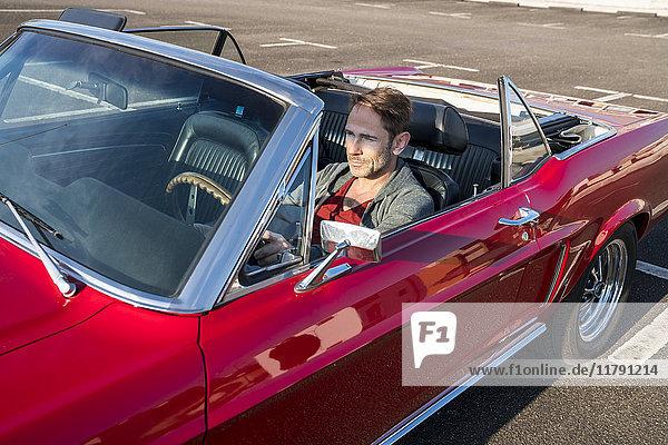 Erwachsener Mann in seinem roten Sportwagen.