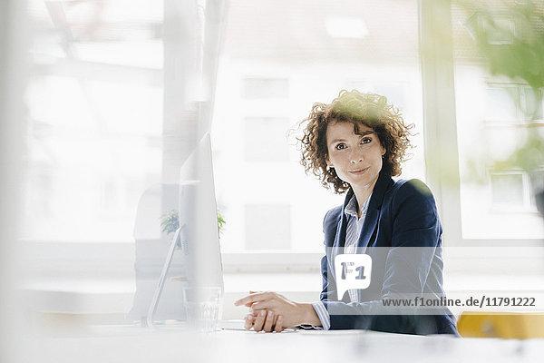 Geschäftsfrau im Büro am Schreibtisch sitzend