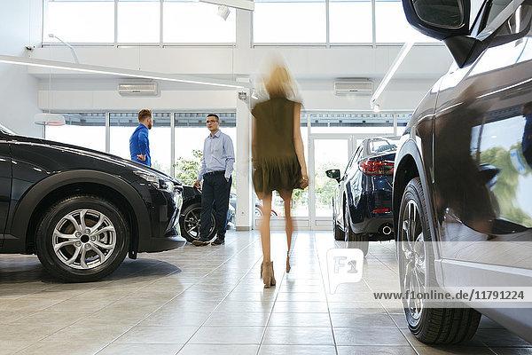 Autohaus im Kundengespräch mit Frau im Vordergrund