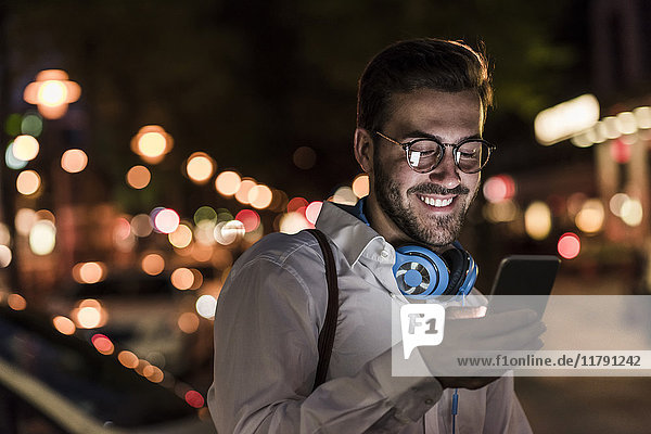 Smiling young man in the city checking cell phone at night