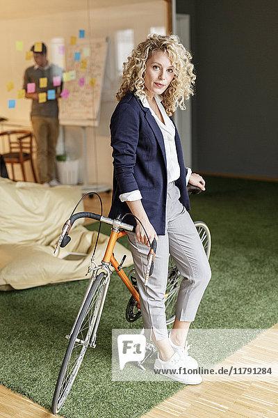 Porträt einer Frau mit Fahrrad im Büro