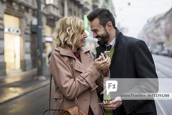 Glückliches Geschäftspaar mit Handys in der Stadt
