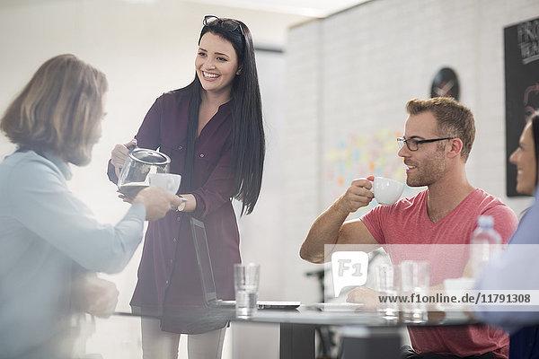 Mitarbeiter gießt Kaffee in die Tasse für Kollegen
