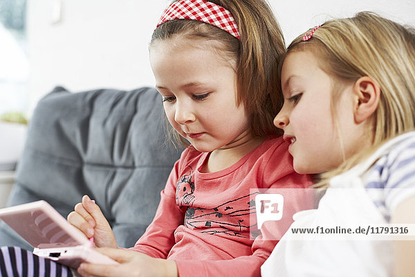 Two little girls sitting side by side on the couch looking at cell phone