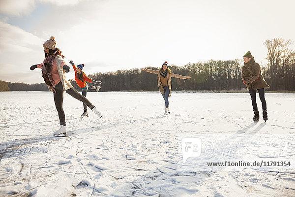 Glückliche Freunde Eislaufen auf dem zugefrorenen See