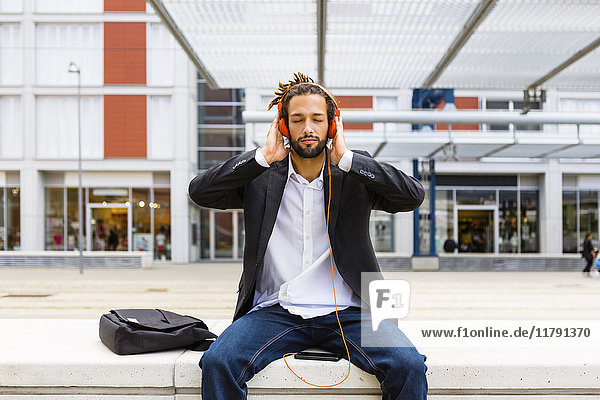Portrait of young businessman with dreadlocks listening music with headphones and cell phone