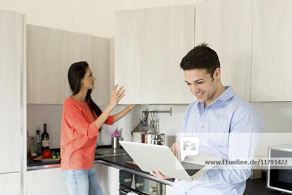 Lächelnder junger Mann mit Frau in der Küche mit Laptop