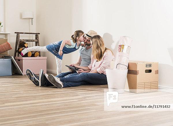 Eltern und Tochter mit Tablette im neuen Zuhause