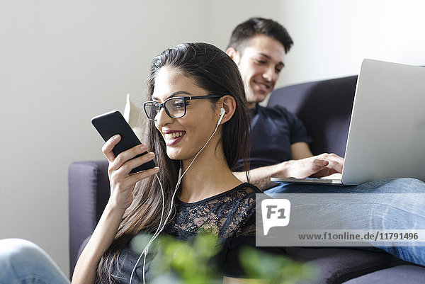 Junge Frau am Telefon im Wohnzimmer mit Freund auf der Couch im Hintergrund