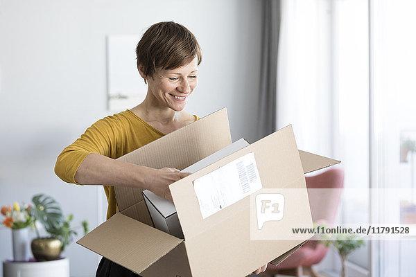 Lächelnde Frau beim Auspacken zu Hause