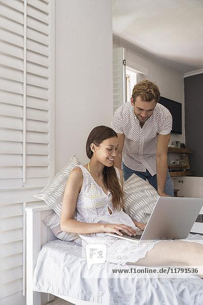 Lächelndes junges Paar mit Laptop im Schlafzimmer