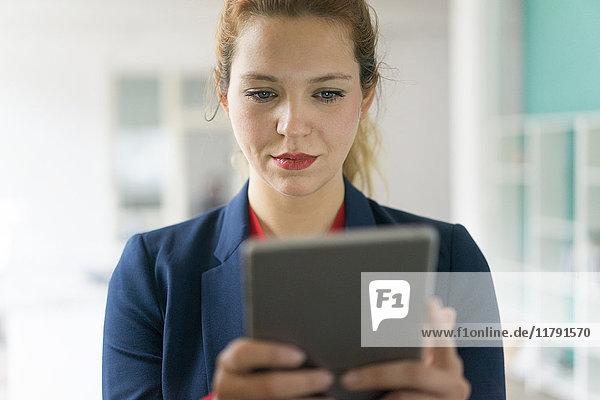 Geschäftsfrau betrachtet digitales Tablett