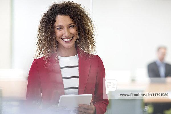 Porträt einer lächelnden Geschäftsfrau mit Tablette im Büro
